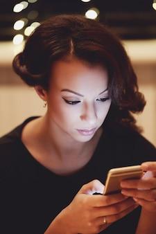 Женщина в ресторане с помощью смартфона