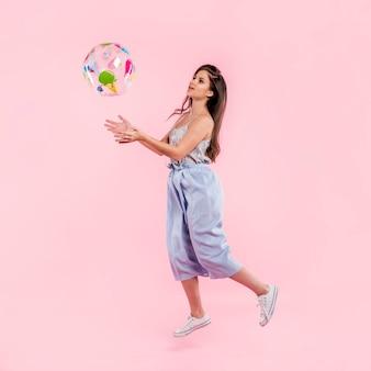 Женщина в комбинезон играет с пляжный мяч