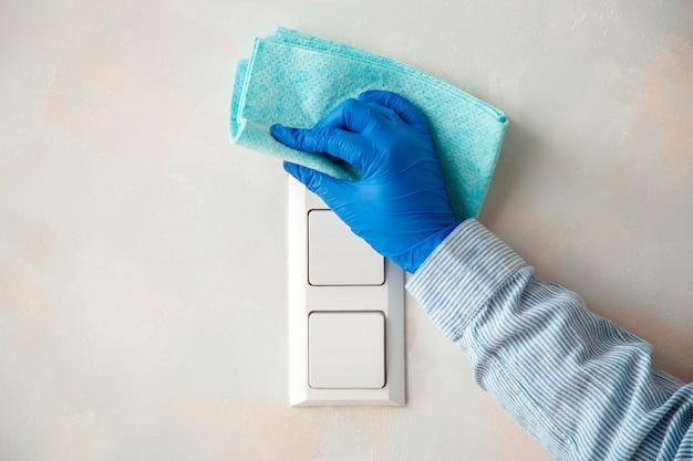 濡れた雑巾で壁に布を付けた、ゴム製の青い手袋のきれいな光スイッチの女性新しい通常のcovid 19コロナウイルスの消毒、家の掃除。表面消毒。家事掃除サービス。