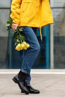 黄色い花のクローズアップとゴム長靴の女性