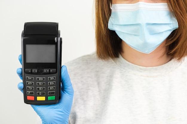 Женщина в резиновых перчатках и маске держит pos-терминал для оплаты во время пандемии