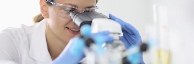 고무 장갑과 보호 화학 안경에 여자는 실험실 초상화에서 현미경을 통해 보인다. 임상 진단 분석 개념을 수행합니다.
