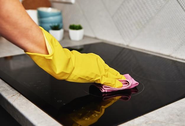 Женщина в резиновых перчатках чистит индукционную плиту