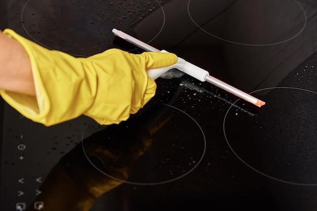 誘導ストーブを掃除するゴム手袋の女性