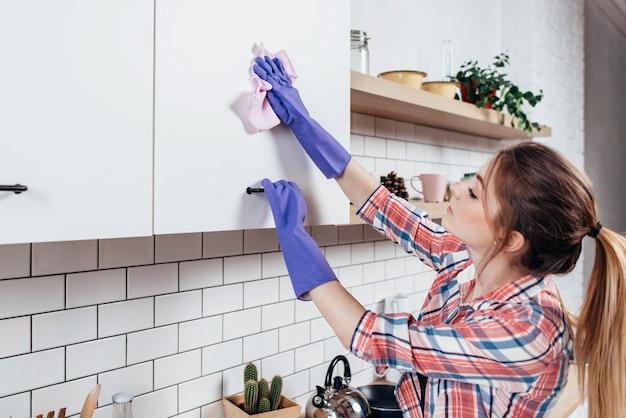 キッチンキャビネットを掃除するゴム手袋の女性。