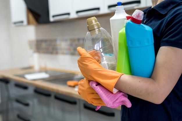 台所で洗浄液のペットボトルを保持しているゴム手袋の女性。家の掃除のコンセプト。