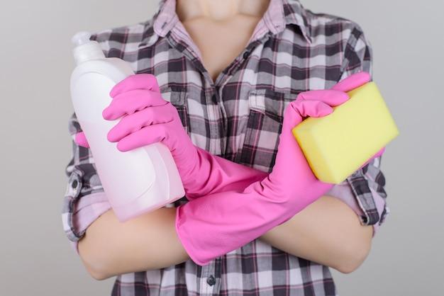Женщина в резиновых перчатках со скрещенными руками держит бутылку желтой губкой на изолированном сером фоне