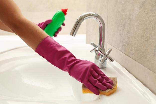 Женщина в розовых резиновых перчатках чистит раковину