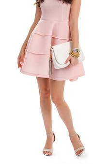 연어 드레스에 여자입니다. 흰색 가방과 베이지색 힐. 주름이 있는 세련된 칵테일 드레스. 소녀는 캐주얼한 저녁 복장을 입습니다.