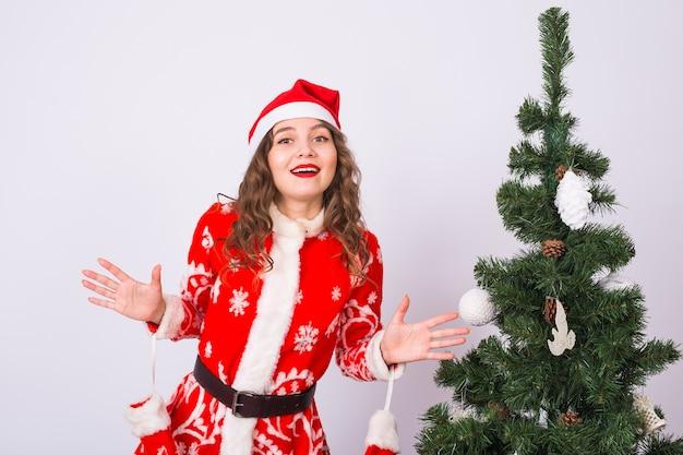 Женщина в костюме санта-клауса возле елки