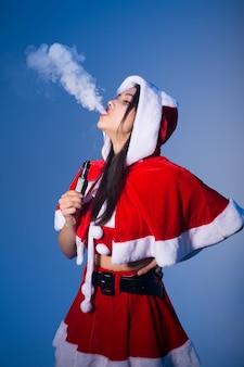 Женщина в костюме санта-клауса курит электронную сигарету и выдыхает белый пар на синем фоне