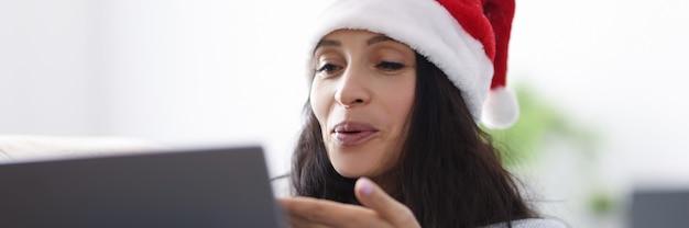 サンタクロースの帽子をかぶった女性が笑顔でラップトップコンピューターにキスを吹く