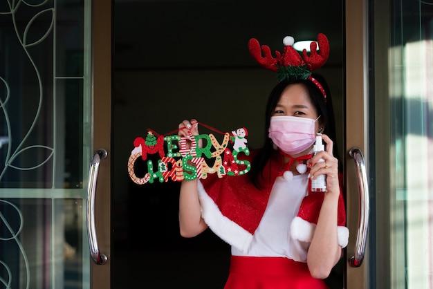 Женщина в костюме санта-клауса с маской для лица и держит спрей от алкоголя в рождественский день