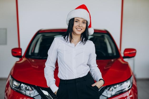 자동차 쇼 룸에서 빨간 자동차로 산타 모자에있는 여자