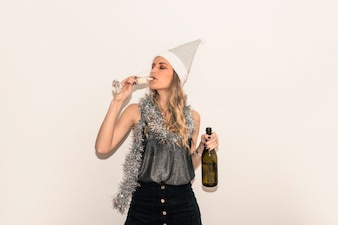 Woman in Santa hat drinking champagne from glass
