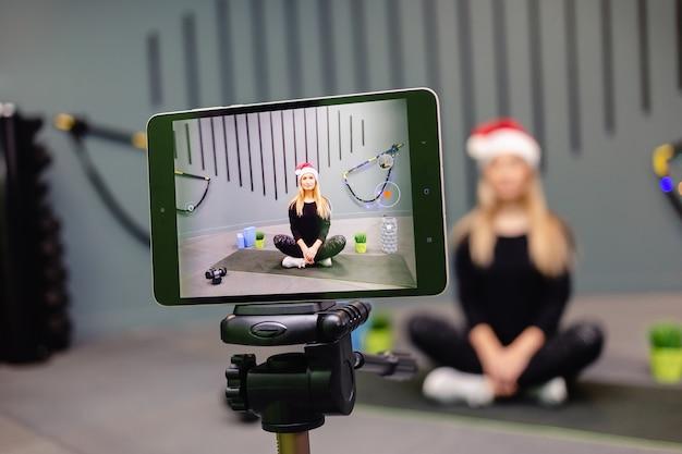 삼각대에 카메라를 사용하여 비디오 블로그를 기록하는 산타 모자 피트니스 트레이너의 여자.