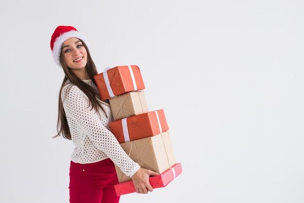 - コピースペースのある白い背景にたくさんのプレゼントを持ったサンタ帽子の女性