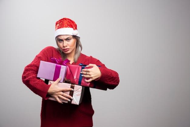 ギフトボックスの束を保持しているサンタ帽子の女性。