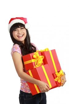 Женщина в новогодней шапке держит рождественские подарки