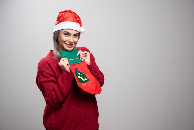 クリスマスの靴下を保持しているサンタ帽子の女性。