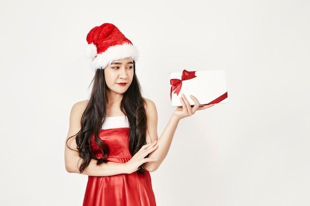 Женщина в шляпе санта держит подарки