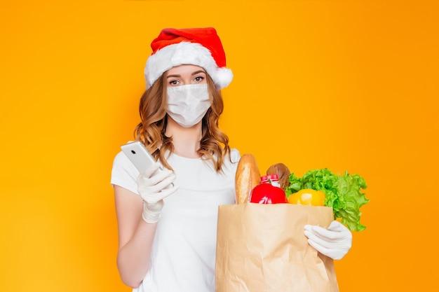 サンタの帽子をかぶった女性は、携帯電話、食べ物、野菜、果物、コショウ、ヨーグルト、サラダ、ハーブ、パンが入った紙袋を持っています
