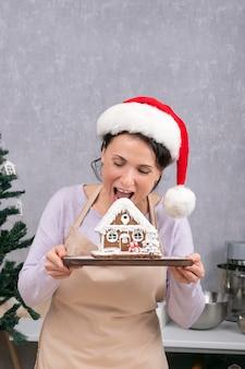 サンタの帽子をかぶった女性がジンジャーブレッドハウスを持って噛もうとします。垂直フレーム。