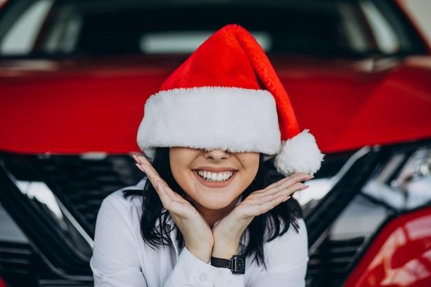자동차 쇼 룸에서 크리스마스에 산타 모자에있는 여자