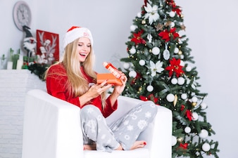 Woman in Santa hat opening small gift box