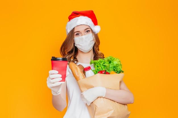 산타 모자에있는 여자, 보호 마스크는 제품, 야채와 함께 종이 봉지를 보유하고 커피 한 잔을 보여줍니다.