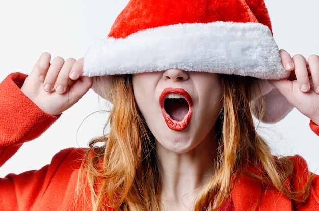 休日をポーズするサンタ帽子赤い唇の感情の女性