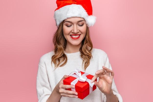 Женщина в шляпе санта улыбается и держит красную подарочную коробку
