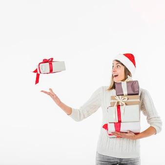 Woman in Santa hat throwing gift box