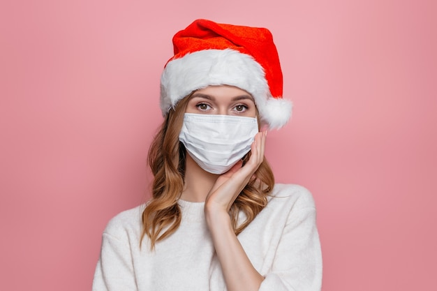 Женщина в шляпе санта-клауса в медицинской респираторной защитной маске