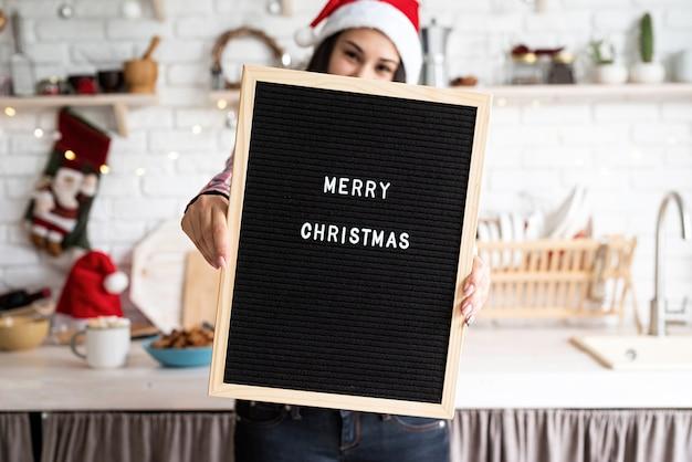 メリークリスマスという言葉で黒い文字板とサンタ帽子の女性