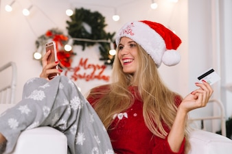 Woman in Santa hat with phone and card