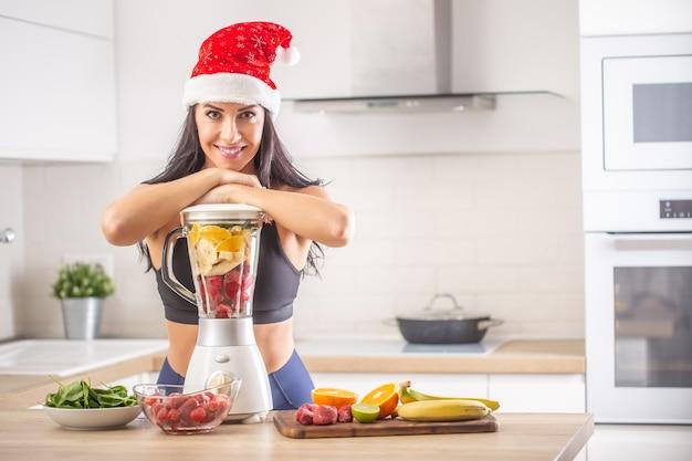 サンタの帽子をかぶった女性は、スムージーに変える準備ができているフルーツのカラフルなミックスでブレンダーに寄りかかっています。