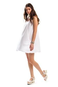Идет женщина в сарафане. белая одежда и сандалии. вид сбоку привлекательной модели. легкий и удобный наряд.