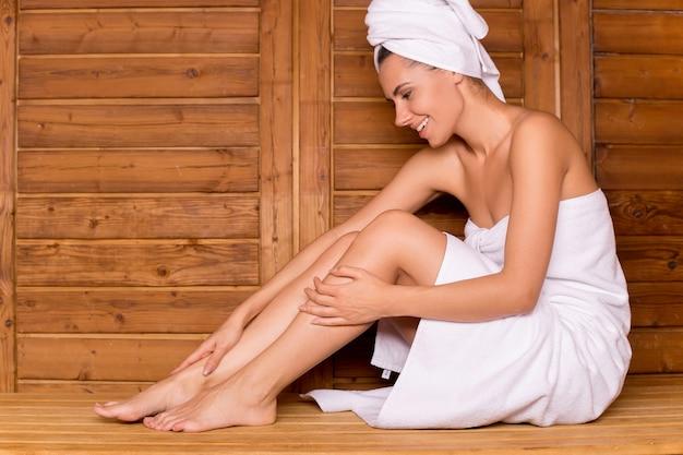 Женщина в сауне. привлекательная молодая женщина, завернутая в полотенце, расслабляется в сауне и улыбается