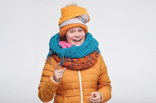 スカーフと帽子の彼女の友人の冗談で笑ってカメラを指して女性