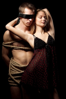 Женщина в сексуальном ночном платье обнимает своего партнера-мужчину с обнаженным телом, покрытым веревками в темной комнате