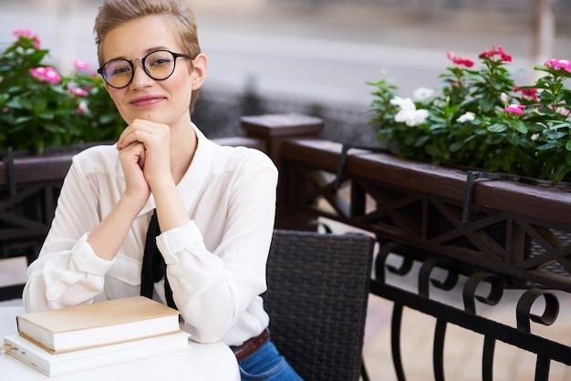 Женщина в рубашке и галстуке за столом книга образование интерьер цветы