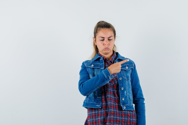 셔츠에 여자, 오른쪽을 가리키는 재킷과 화가, 전면보기를 찾고.