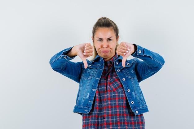 シャツを着た女性、二重の親指を下に向けて不満を感じているジャケット、正面図。