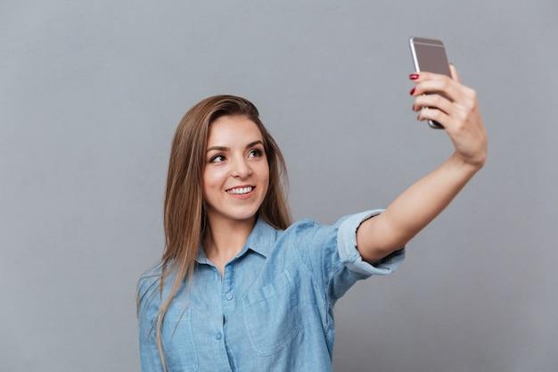スマートフォンでselfieを作るシャツの女性