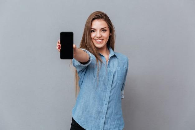 空白のスマートフォンの画面を示すシャツの女性