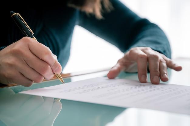 Женщина в рубашке подписывает документ