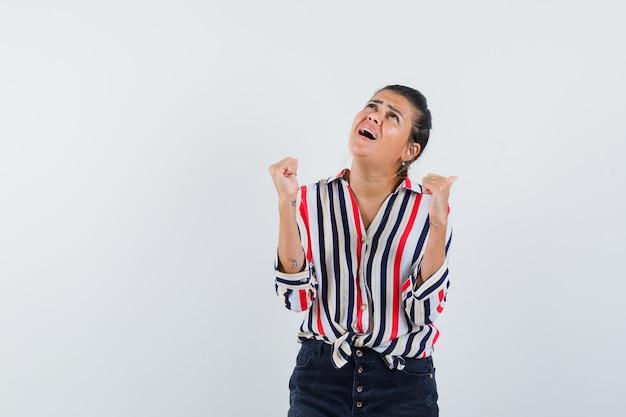 Женщина в рубашке, юбке показывает жест победителя и выглядит счастливой