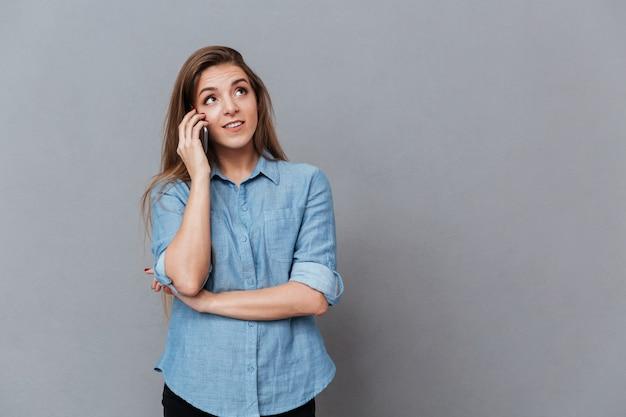 電話で話しているシャツの女性