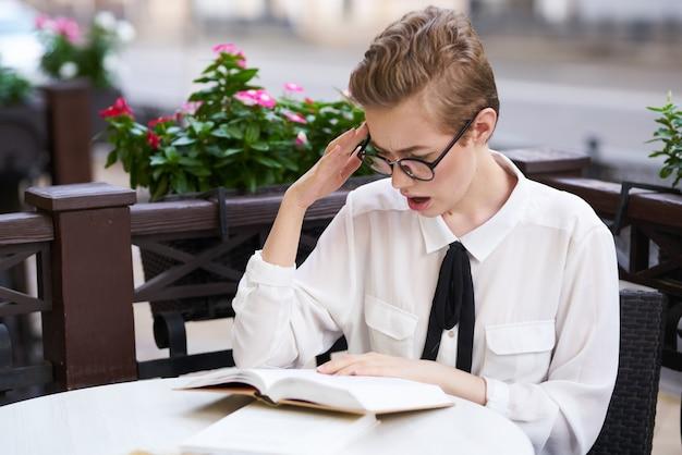 シャツを着た女性は、顔の教育科学のオープンブックのカフェグラスのテーブルでネクタイをします。高品質の写真